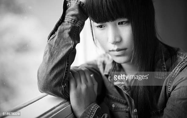 アジア人のティーンエイジャーの女の子に座ってウィンドウ、悲しみます。
