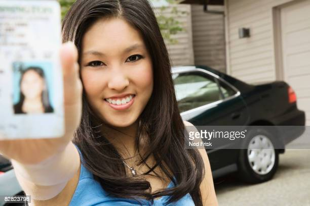 Asian teenager proudly showing new driver's license