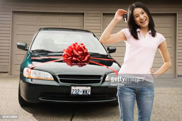 Asian teenager with keys to new car