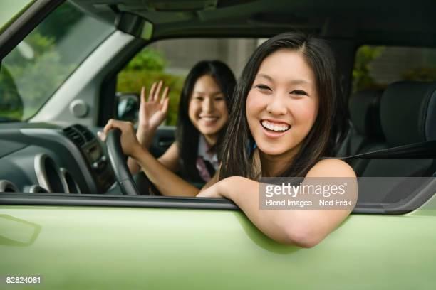 Asian teenagers driving in car