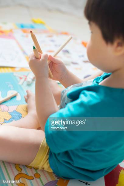 Asian toddler boy choosing colour pencil.