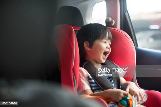 Asian toddler boy singing in the car on baby car seat.