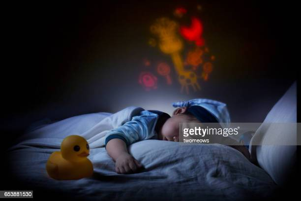Asian toddler boy sleeping in the dark.