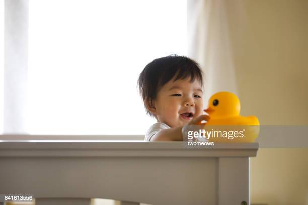 Asian toddler boy with rubber duck.