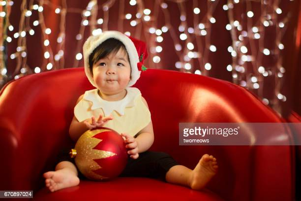 Asian toddler in Christmas outfit making a face sitting on red arm chair