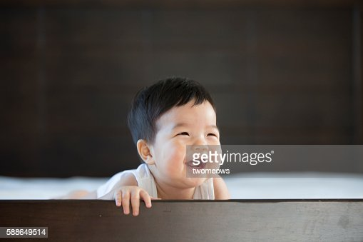 Asian toddler laughing in bed.
