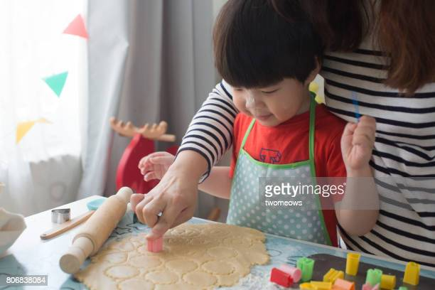Asian toddler learn to bake cookie with mother.