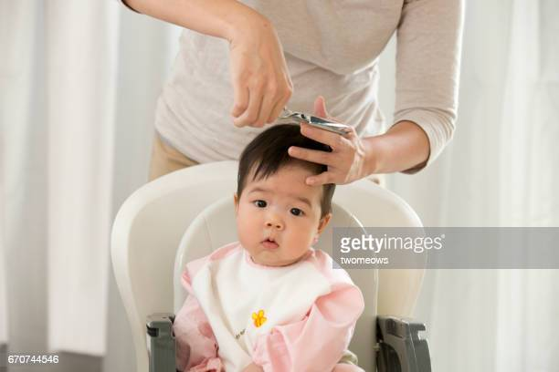 Asian toddler looking stressed by mother trimming his hair.