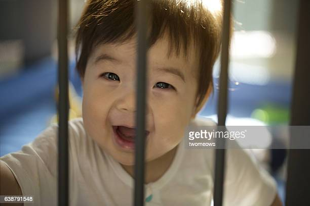 Asian toddler looking though play pen.
