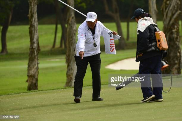 Asian Tour Tournament Director Wanchai Meechai showed the workers to clean the green with the blower during round two of the UBS Hong Kong Open at...