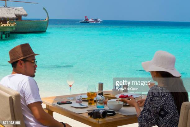 Asian tourist couple is having Breakfast at the Lifestyle Resort Milaidhoo Island BaaAtoll on and looking to Traditionial Boats and a Seaplane on...