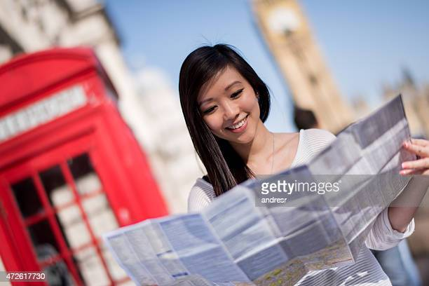 Asian tourist in London holding a map