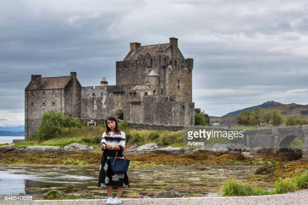 Asian tourist taking selfie with smartphone camera on selfie stick in front of Eilean Donan Castle in Loch Duich Ross and Cromarty Western Highlands...
