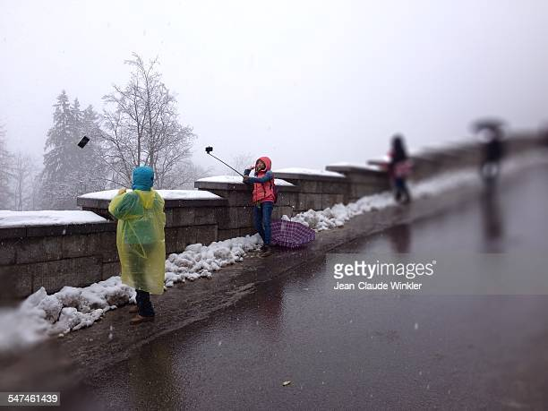 asian tourists taking selfies with selfie sticsk on rainy winter day in Bavaria Germany