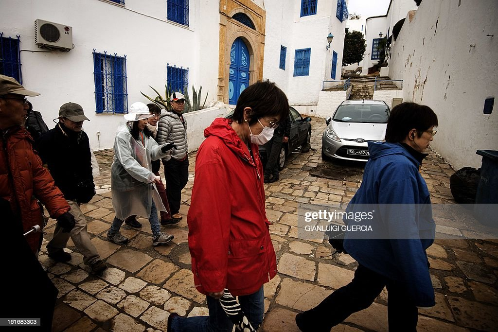 Asian Tourists walk through the streets of the hilltop village of Sidi Bou Said on the outskirts of Tunis on February 12, 2013. Sidi Bou Said, named after the mausoleum outside the Tunisian capital, is a popular tourist destination known for its narrow streets and traditional houses with blue doors and cafes that attract foreigners and locals.
