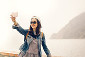 Beautiful Asian traveler taking selfie with ocean view background, soft warm light tone