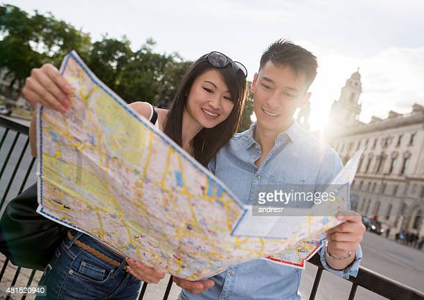 Asian travelers holding a map in London