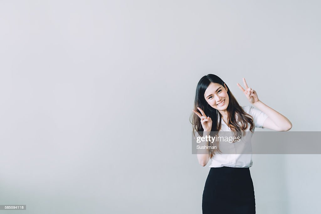 Idee Pose Fotografiche : Asian university girl doing funny rabbit pose with copy space