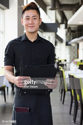 Asian waiter standing in restaurant