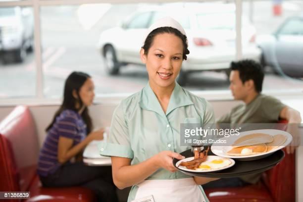 Asian waitress holding tray of food