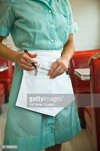 Asian waitress putting order pad in apron