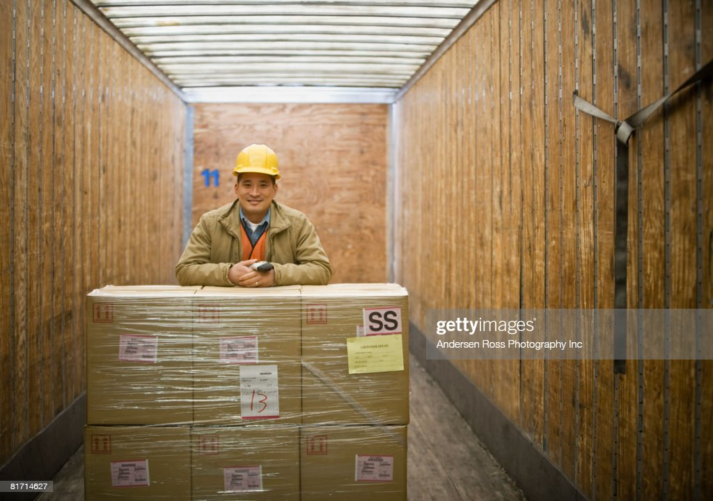 Asian warehouse worker with shipment in truck : Stock Photo