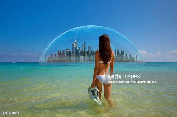 Asian woman admiring city in tropical water