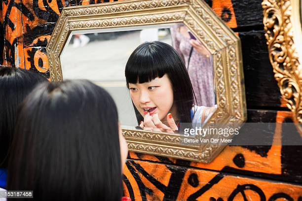 Asian woman applying lipgloss in mirror on market.