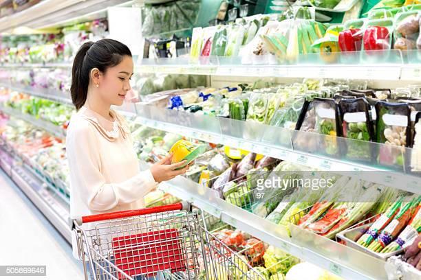 Mulher asiática com muita atenção considera produtos hortícolas na loja