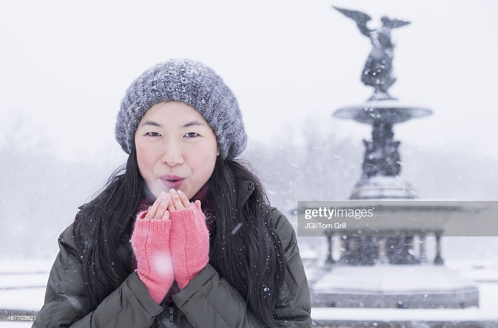 Asian woman blowing on hands in snow