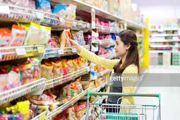 Asian woman buys in the supermarket candy