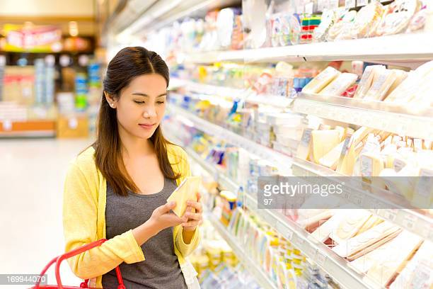 Asian woman buys in the supermarket cheese.