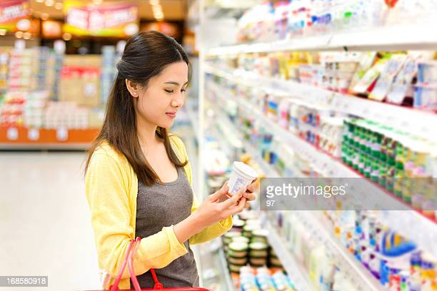 Asian woman buys in the supermarket yogurt.