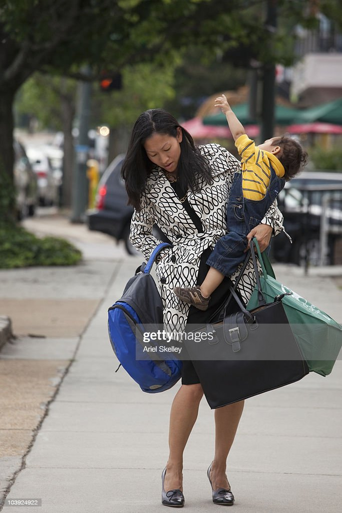 Asian woman carrying baby and bags