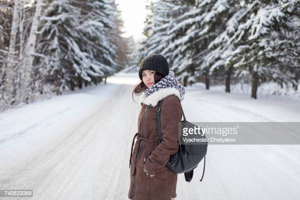 Asian woman carrying backpack on snowy road