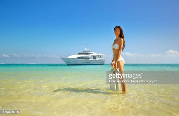 Asian woman carrying fins on tropical beach