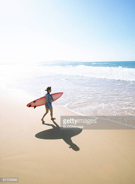 Asian woman carrying surfboard on beach