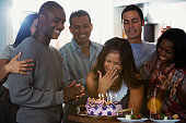 Asian woman celebrating birthday with multi-ethnic friends