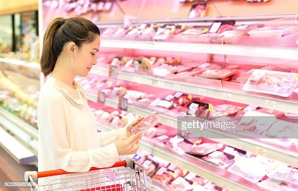 Asian woman chooses meat in the store.
