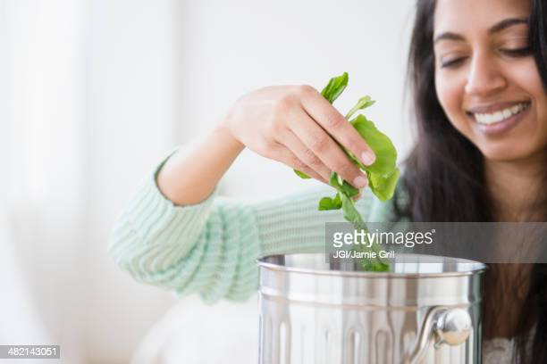 Asian woman composting lettuce