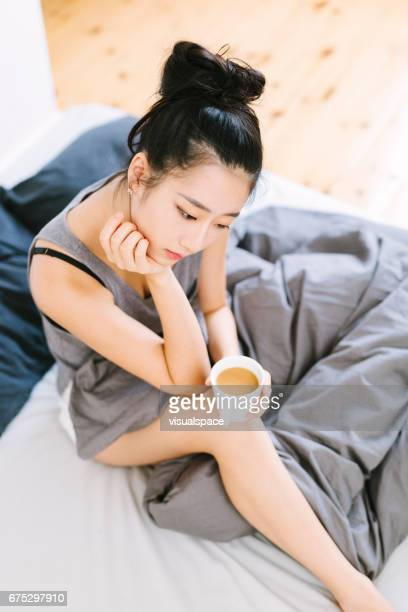 Asian Woman Contemplating in Bed