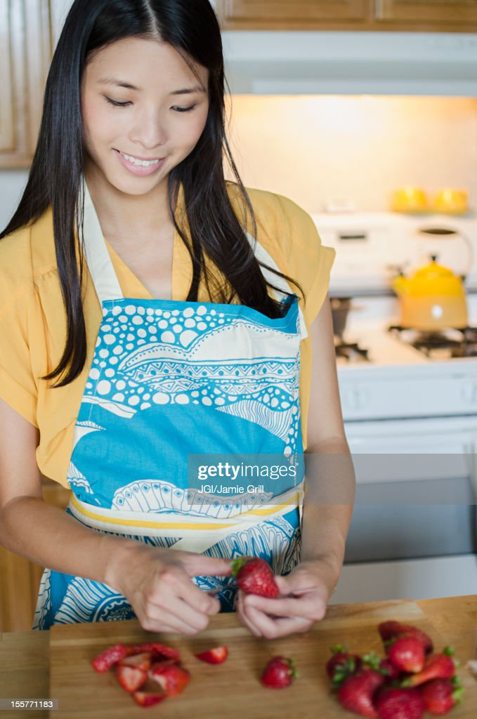 Asian woman cutting strawberries : Stock Photo