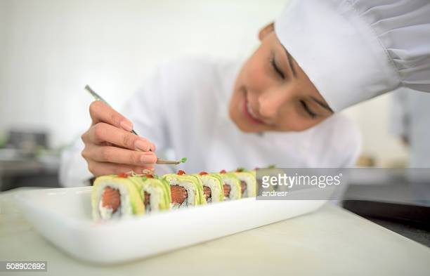 Asian woman decorating a plate
