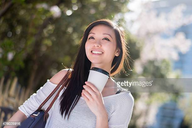 Asian woman drinking coffee on the go