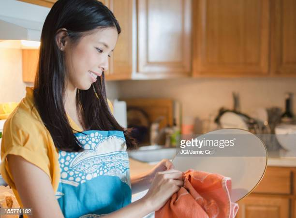 Asian woman drying plate