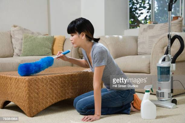 Asian woman dusting coffee table