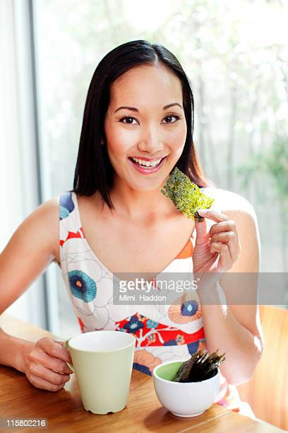 Asian Woman Eating Dried Seaweed at Kitchen Table