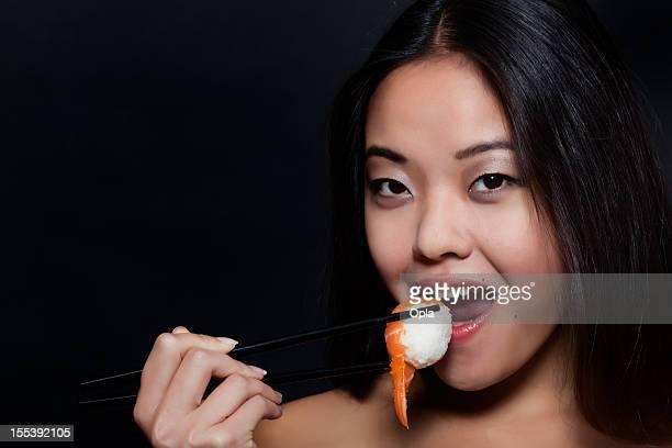 Asian woman eating sushi