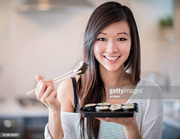 Asian woman eating sushi