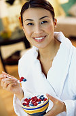 Asian woman eating yogurt with berries